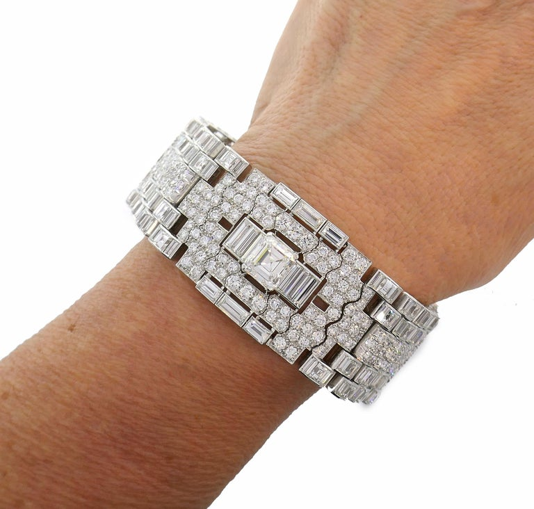 Stunning Art Deco Revival bracelet created in the 1960s. It is made of platinum, features three emerald cut diamonds and encrusted with round brilliant and step cut diamonds. The three larger emerald cut diamonds are: the diamond in the center