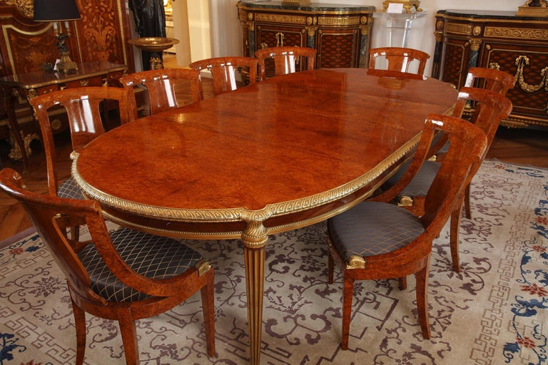 Elegant Louis XVI style dining room set, composed of:  – A beautiful and large table whose tray and transom are belted with a finely chiseled gilded bronze frieze, resting on four brass fluted feet. Measures: Height 75 cm (29.5 in.), width 128 cm