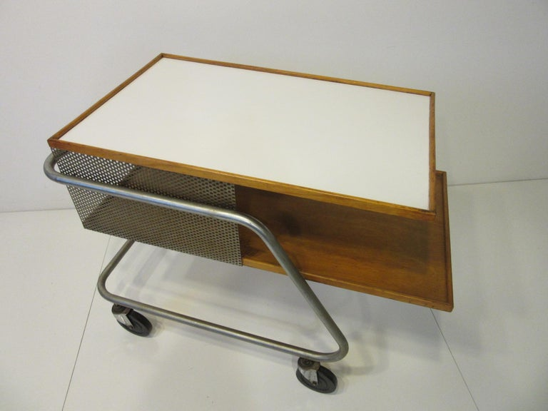 A perforated metal and wood bar / service cart with laminate top and rubber wheels rolling around on a steel tube frame. Franziska the designer studied Bauhaus design at Harvard under Gropius, Kepes, Moholy- Nagy and Breuer. This piece garnered wide