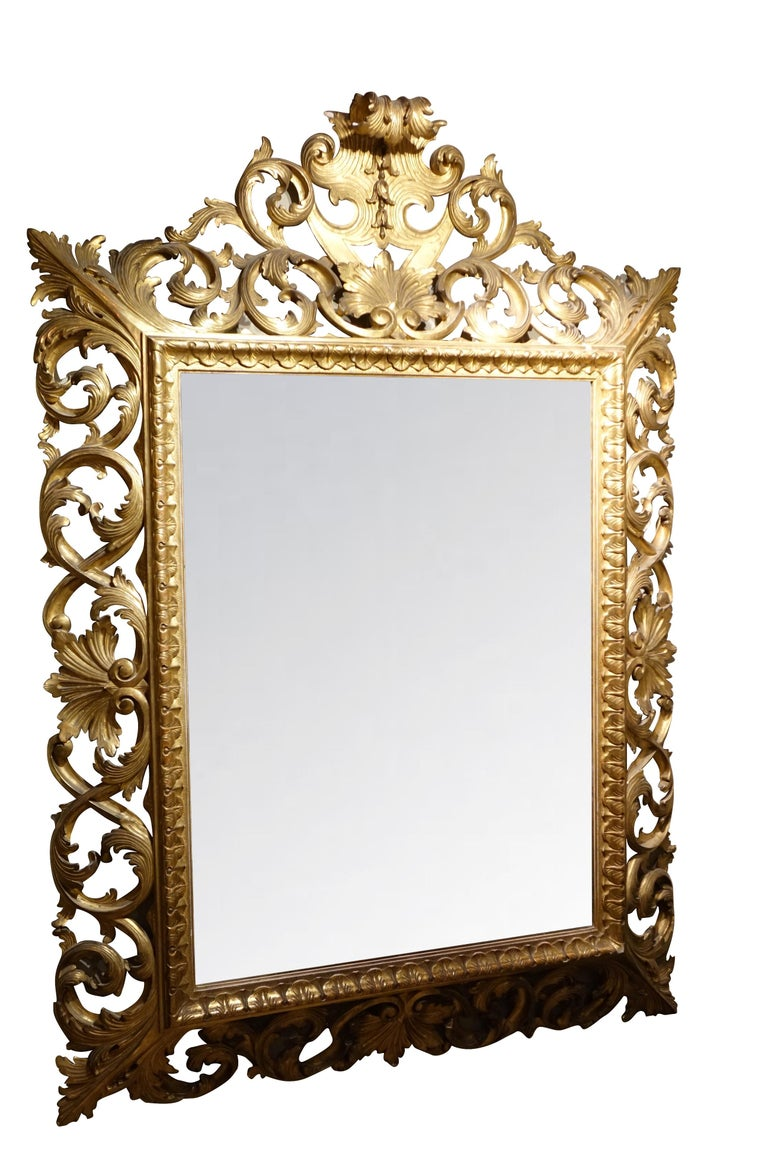 Important mirror in inverted profile, finely carved in an openwork of curls and foliated foliage scrolls.