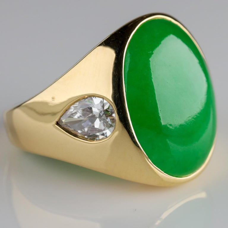 This substantial 18k yellow gold ring features a large (19.1 mm X 13.8 mm X 3.90 mm) Burmese jadeite jade cabochon of vivid apple-green coloring and high translucency —a superb, old-mine stone. The sides of the ring feature a pair of white and