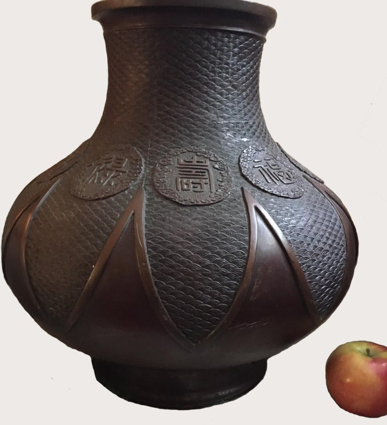 The pear shaped body is rising from the short splayed foot to a waisted neck and flared mouth. The excellent, masterfully casted bronze is decorated with the finest seigaiha pattern. Rich warm brown patina completes the beauty of this Chinese style