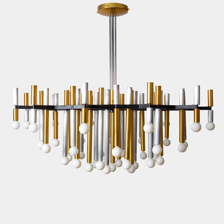 Important large 43-light Stilnovo chandelier, model 1155/43, with alternating brass and aluminum tubular arms suspended from black enameled aluminum structure, Italy, circa 1955. There are two tiers of brass and aluminum tubes separated by the