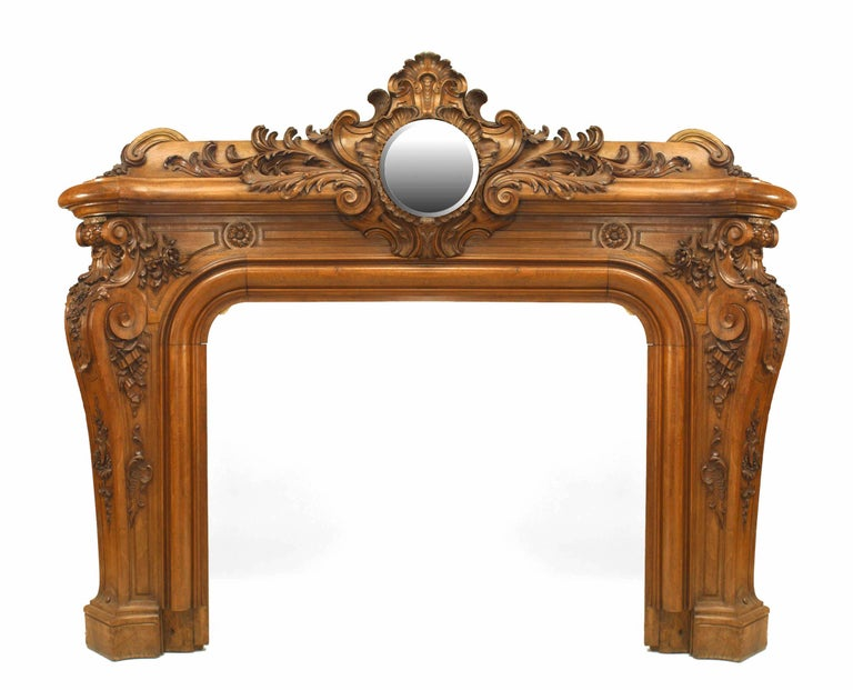 Reputedly from the library of Napoleon III, this large French Louis XV style fireplace mantel is composed of walnut carved curvilinearly with robust foliate designs and scrollwork that culminate in a dramatic raised pediment inset with a circular