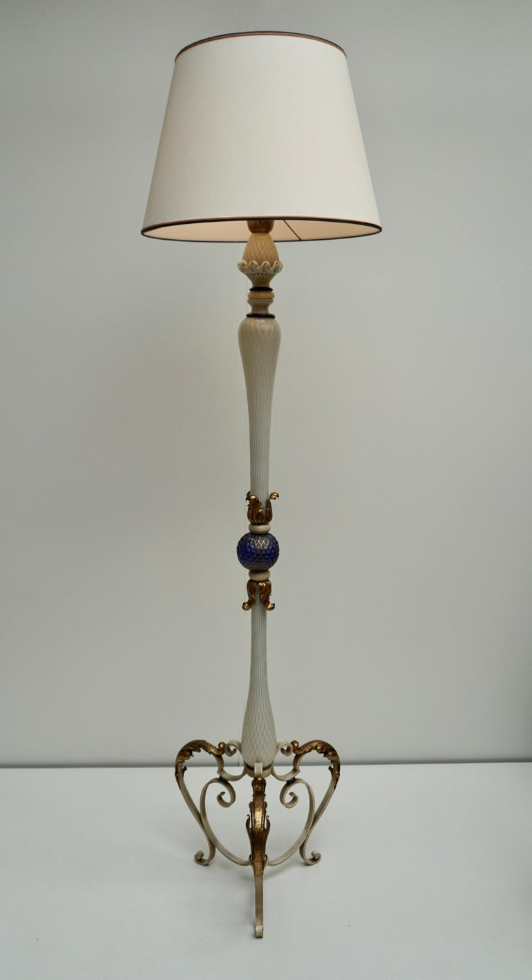 Elegant Italian Murano glass floor lamp with gold inclusion glass in white blue with a white metal base decorated with gilded ornaments.