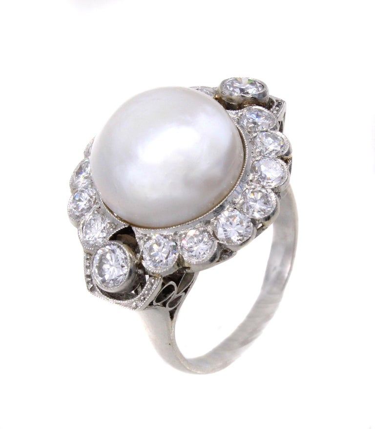 Beautifully designed and masterfully handcrafted, this platinum ring features a centrally set natural saltwater pearl measuring 12.65 x 12.40 millimeters. The pearl is accompanied by a report from the GIA. Natural saltwater pearls measuring over 9