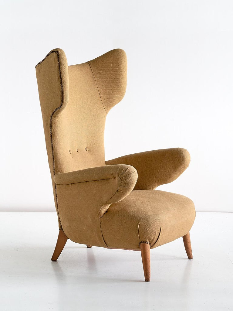 This exceptional wingback chair was designed by Ottorino Aloisio in 1957. The chair was manufactured by the Turin workshop of Pier Luigi Colli.   The organically curved lines of the winged back and the armrests create a striking and elegant
