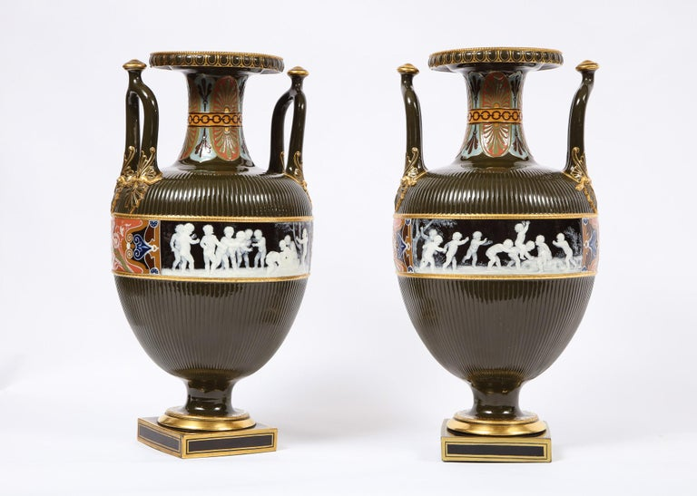 A magnificent and very large pair of antique Minton porcelain Pate Sur Pate vases with multi-paneled neoclassical scenes. In a gorgeous neoclassical style Amphora form with an olive green body, further adorned with beautiful multicolored red, blue