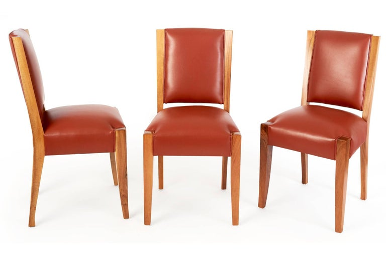 André Sornay (1902 – 2000)  Elegant set of six minimalist, pure-lined dining chairs by André Sornay, with subtly curved and tapered backs and legs. In French walnut with seats upholstered in warm burnt umber leather. The chairs' clean, resolutely