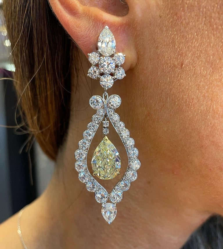 Van Cleef and Arpels Fancy Yellow Diamond Earrings Fancy Yellow Pear Modified Brilliant-cut Colored Diamonds one 7.02 and the other 7.01 carats, Surrounded by Pear-shape and circular-cut Diamonds Signed Van Cleef & Arpels and numbered The earrings