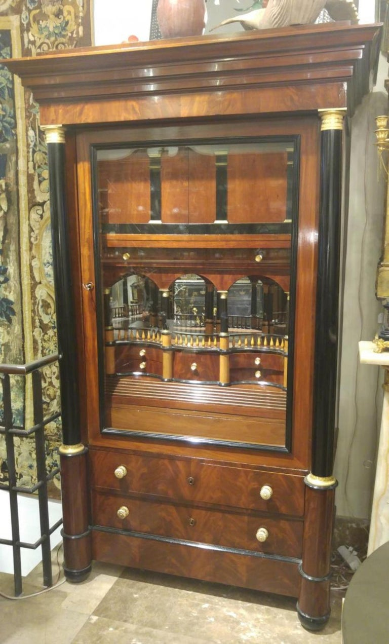 Secretarial closet of architectural moon of cornice flown.   Cornice free of flat frieze on ebony pilasters with Doric capitals in gilded bronze.   Desk with interior baluster bins in birch turned.