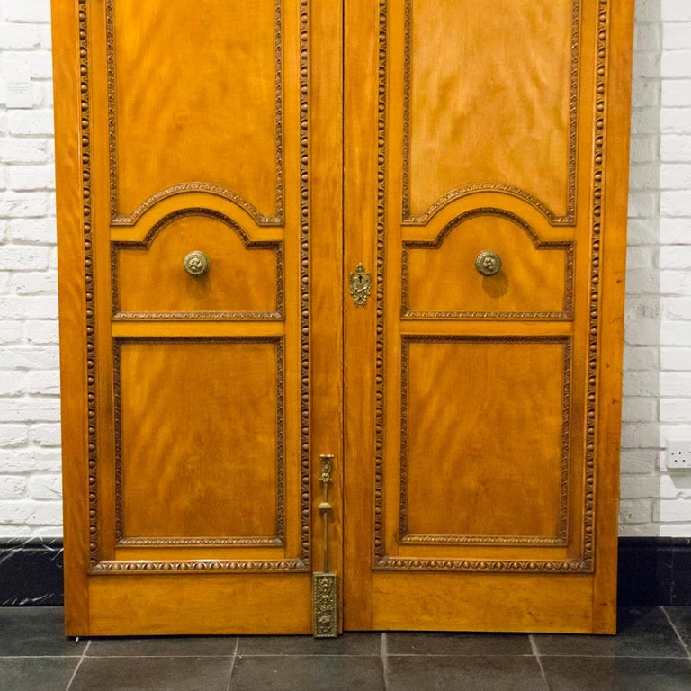 A pair of monumental solid satinwood doors with classical egg and dart carved decoration and fine quality brass door furniture.  Brass door pulls marked CHING (Comyn Ching of London).  Full set of brass acorn finial hinges included.  Left
