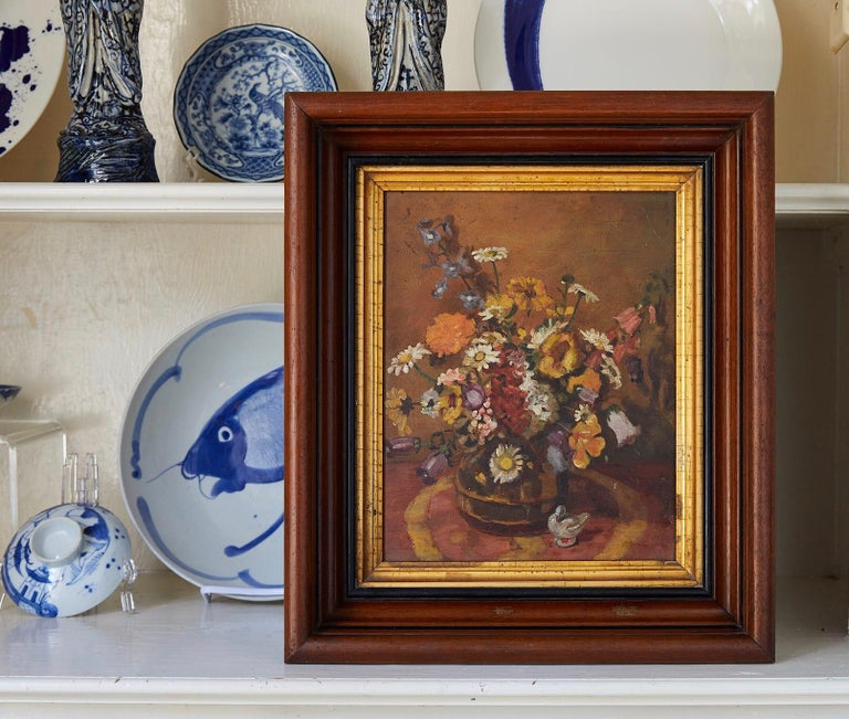 Early 20th century still life of wildflowers in a vase with a white duck figurine on the table in the foreground. The unsigned oil on board is painted in the manner of Impressionism and is held in an antique mahogany frame with gilt wood liner. The