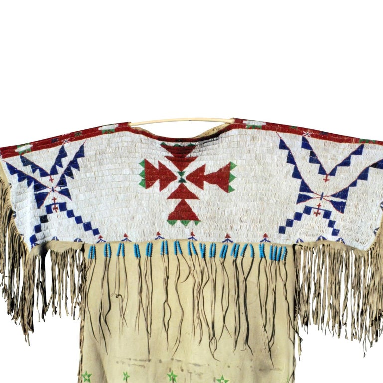 Faceted Beads; Arapaho/Sioux dress on brain-tanned buffalo. Simple four color design; was probably the first dress made after quilling. Stars on dress, and unusual beaded bottom.  Period: 1870s  Origin: Arapaho/Sioux Plains  Size: 42