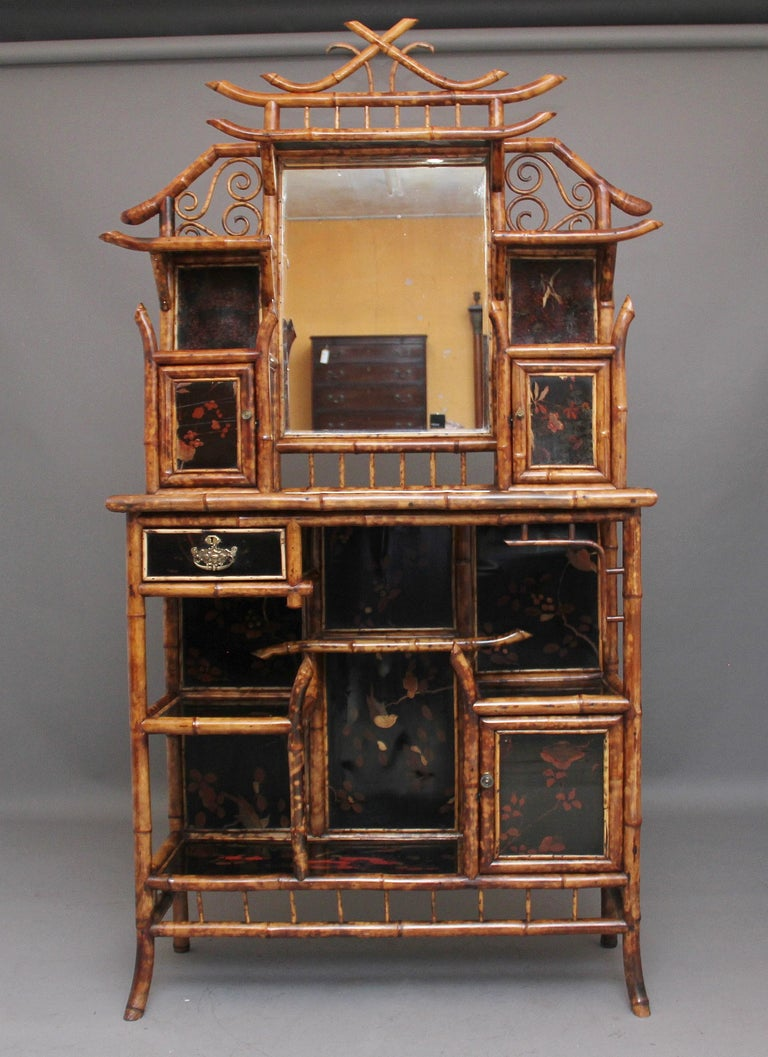 An impressive 19th century bamboo cabinet, having twenty nine original decorative lacquer panels depicting floral scenes, a mirrored shelved back, various cupboards and shelves and a drawer with brass plate handle, the shaped bamboo makes this