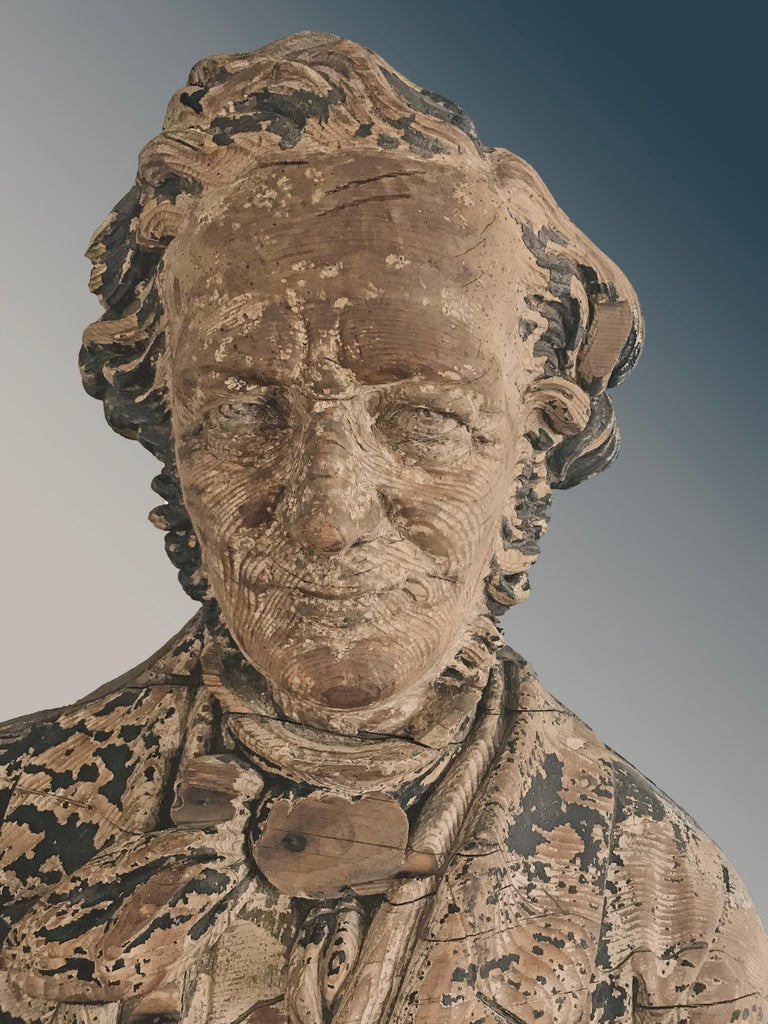 Sternboard carving of a bust, carved in the round, wearing a blue-painted jacket and black tie, with an undershirt. Decorated sternboard carvings were a rarely used counterpart of figureheads, usually they were eagles or some type of decorative