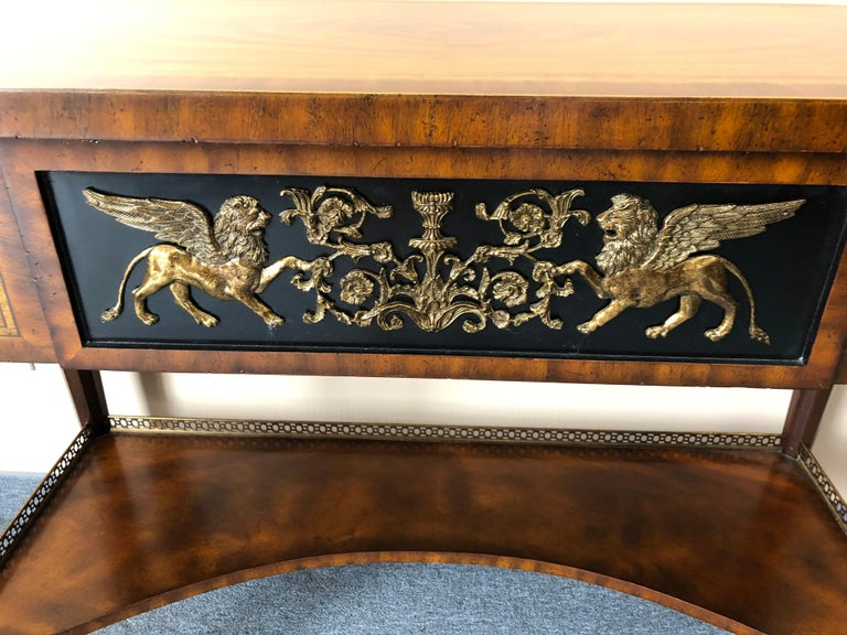 Very rich banded bookmatched crotch mahogany sideboard or console having 3 drawers and gorgeous brass embellishments, especially on the center drawer with winged horses and neoclassical curlicues.
