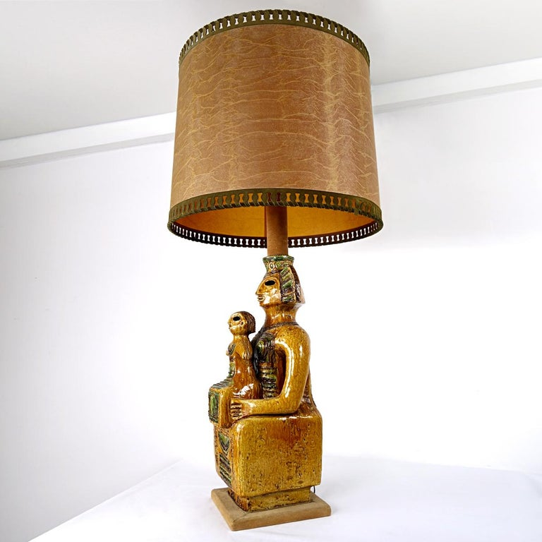 This eye catching floor or table lamp in Mayan style truly is an impressive piece. Its foot is a large ceramic statue of a queen and her child, or a king if you will with his successor, in brown and green shades.  The lower part of the