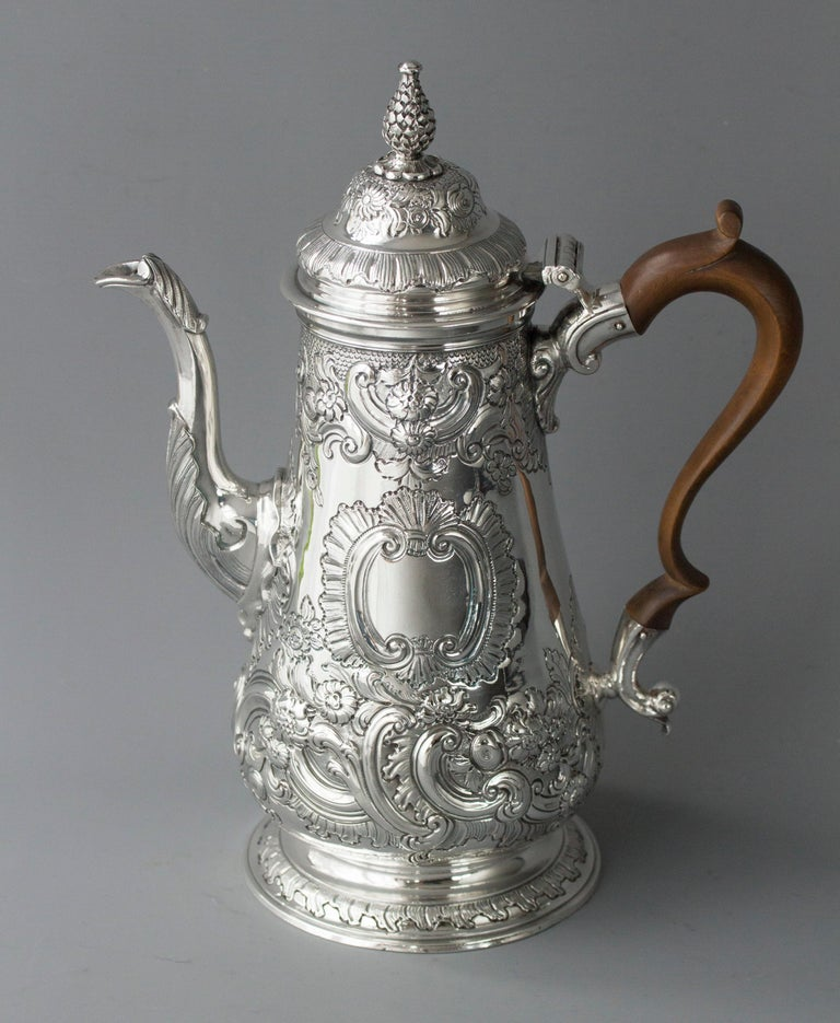 An impressive George II silver coffee pot of tapered baluster form, with a cast and applied spout, surmounted by a raised, domed lid with a cast pinecone finial. Original scroll fruitwood handle. All standing on a raised circular foot. The pot is