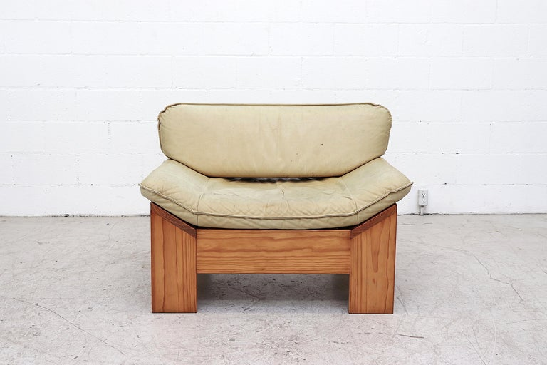 Impressive Leolux pine and leather lounge chair with cream leather cushions. Lightly refinished pine frame in original condition with small repaired rip in back cushion and visible patina including blemishes and discoloration to leather. Awesome