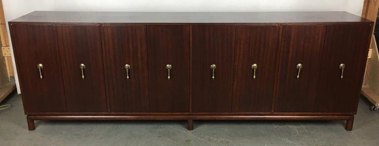 Beautifully crafted mahogany sideboard raised on a dowel-legged base in the style of Monteverdi-Young. This thin-edged piece has four bi-fold door compartments; two are fitted with drawers and felt lined silver storage and the remaining two are