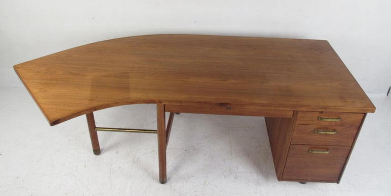 This stunning vintage modern desk features an unusual curved top offering plenty of work space. Quality construction with a finished back and charming walnut wood grain. This wonderful mid-century case piece has ample storage space within its four