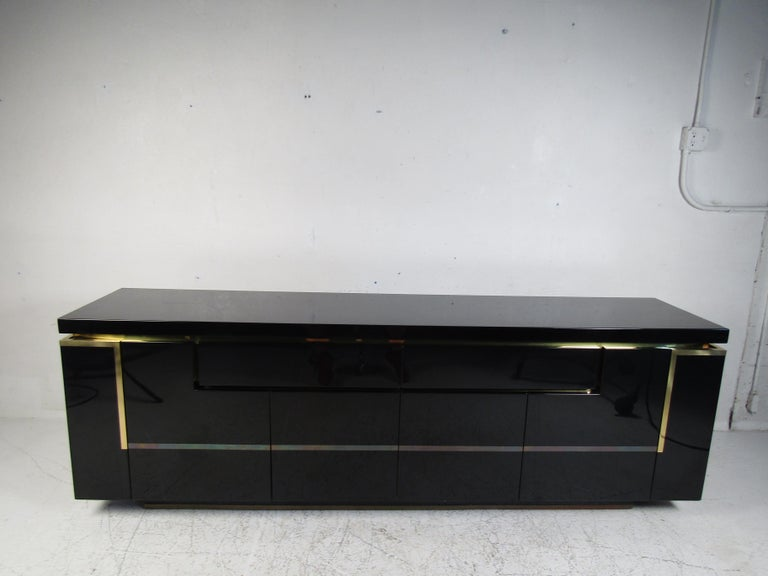 This stunning modern sideboard offers plenty of room for storage within its many compartments. The unique design appears to have interlocking cabinets with the two drawers. The glossy black finish and brass trim add to the allure. A finished back