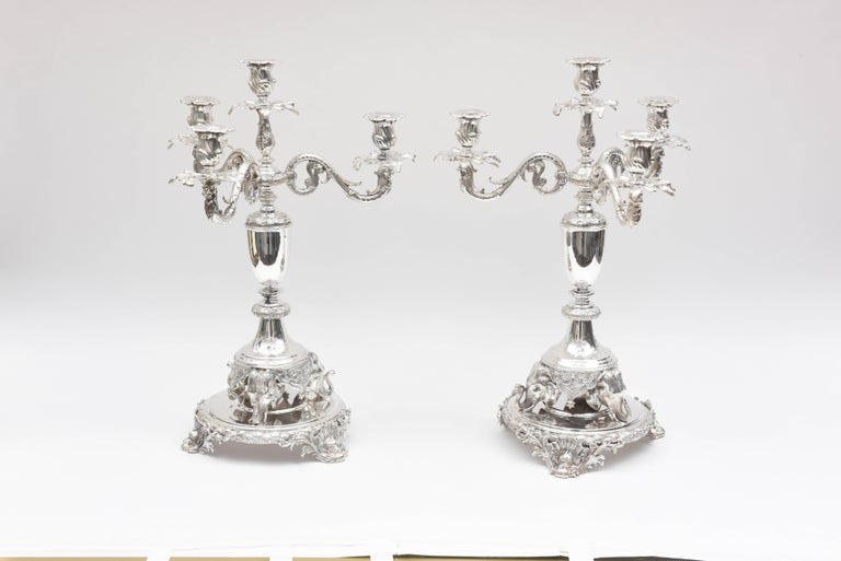 A tall and well chased set of 2 elegant candelabra with figural tripartite elephant feet. They are raised on scrolled platform bases with dolphin and shell flourishes to their feet. They are in fine vintage condition and are show stopping stunning.