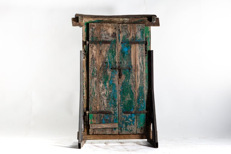 This complete entryway is handsomely carved, with two horse heads greeting visitors from above. The paneled doors open inwardly and can be secured with a sliding bolt and lock mechanism. The whole remains unaltered, coated in its original colorful