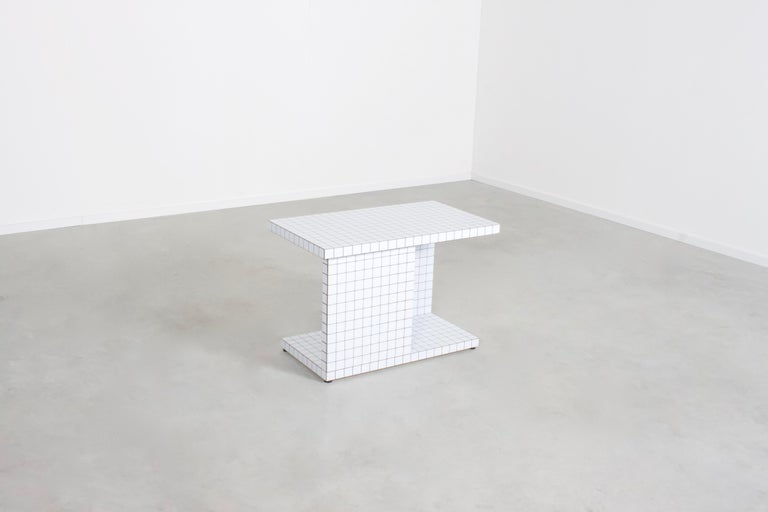 Beautiful 'Quaderna' end table in very good condition.  Manufactured by Superstudio, 1972.  The table is covered with a white plastic laminate, printed with black squares.   The table has two tiers and can also be used to store books for