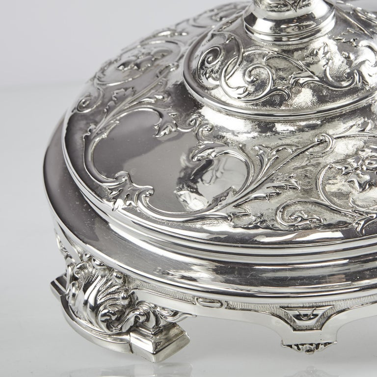 A stunning antique silver bowl or jardinière, based on a classical style with a round pedestal base and oval boat-shaped dish. It is hand-chased with bas-relief entwined leaf and flower decoration and has two scrolling handles cast as stylized