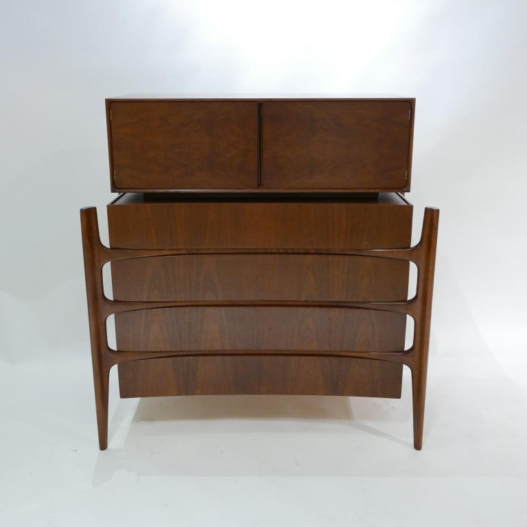 Exposed carved walnut legs with a curved bookmatched walnut front. Beautiful and Sculptural four drawer chest with 2 door top cabinet designed by William Hinn for Urban Furniture's