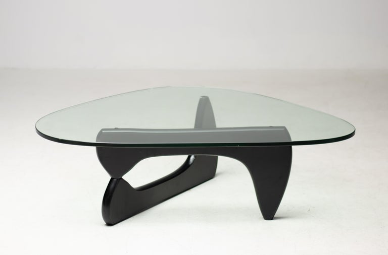 A very early Isamu Noguchi for Herman Miller IN-50 coffee table with original glass top resting on interconnected pivoting black lacquered supports.