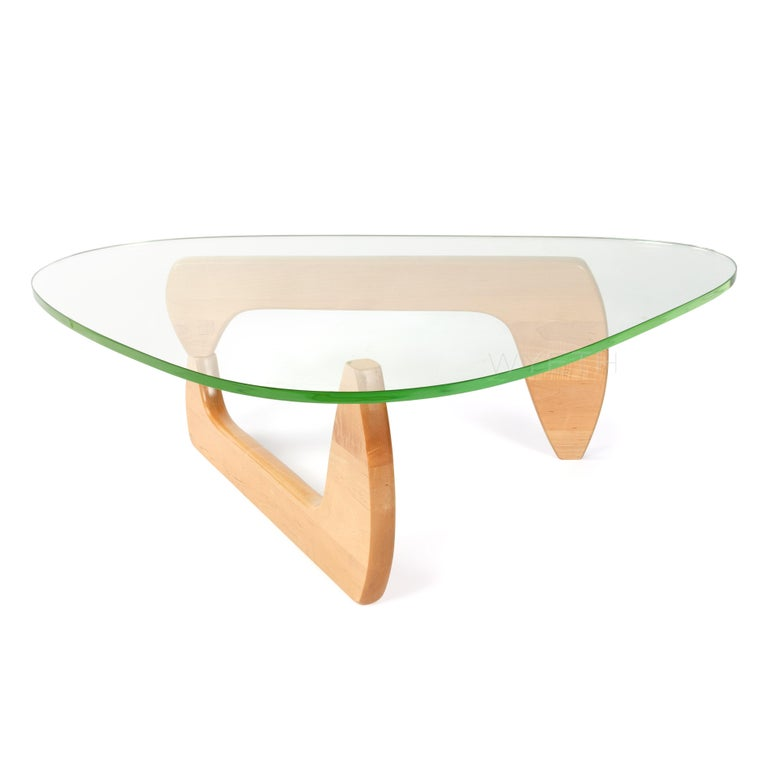 An early IN-50 low table having the original triangular shaped thick glass top resting on a birch pivoting base.