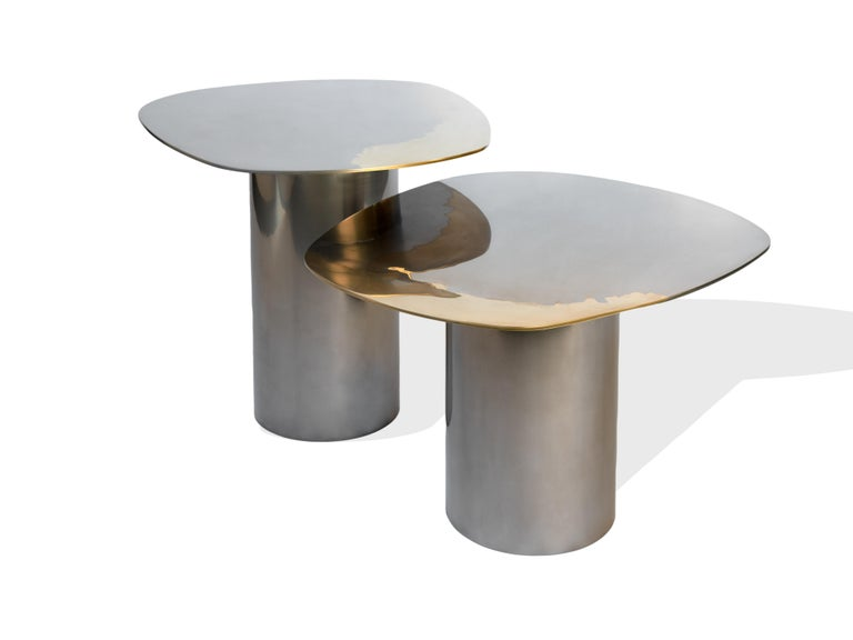 A set of nesting tables as part of the Transition collection, featuring unique, artistic mirror polished tabletops, crafted from brass and stainless steel on tubular bases.   Studio Warm has developed a distinctive, high-end, artistic finish