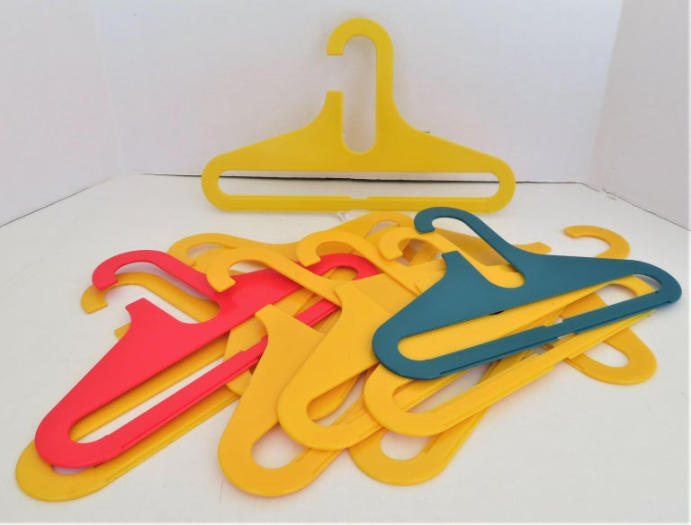 From the 1970s in the style of Ingo Maurer's Op Pop FLAIR colorful heavy plastic clothes hangers. A set of 11 colorful plastic hangers for children clothing, 10 of the same size, 12 1/2 inches wide, and one a bit wider in yellow, 14 1/2 inches wide.