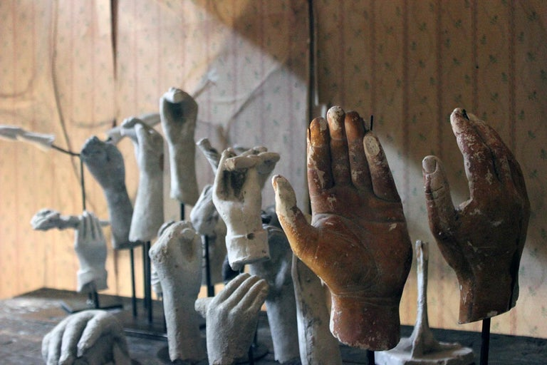 The large group of twenty three plaster moulded maquettes mainly being human hands, digits and legs, some holding flowers, and two being free standing to include an ostrich foot, the others each mounted on five painted steel rod bases and surviving