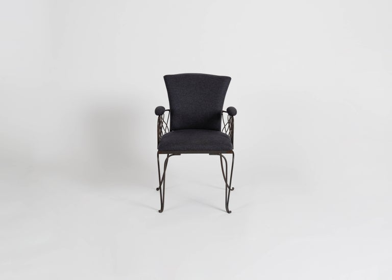 A wrought iron chair in the manner of Jean Pascaud, featuring elegantly splayed feet, a broad back, and crisscrossing supports under each arm.