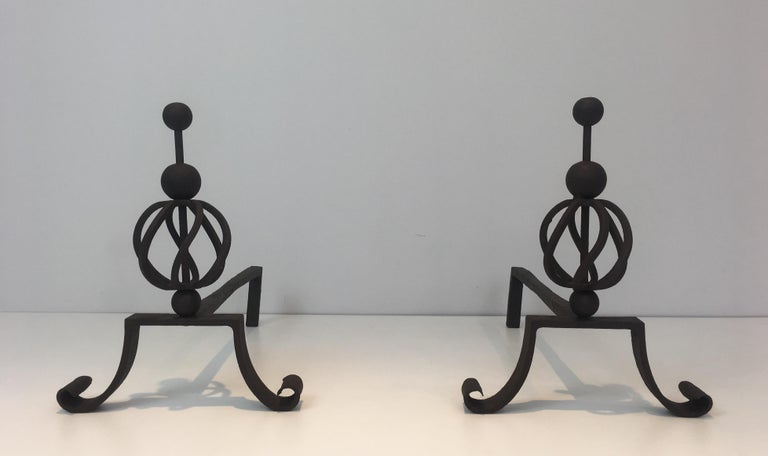 This pair of wrought iron andirons are very elegant and made of a very good quality. It is a french work and the pure lines of this iron work are really in the style of the so famous french designer Jean Royère, circa 1940.