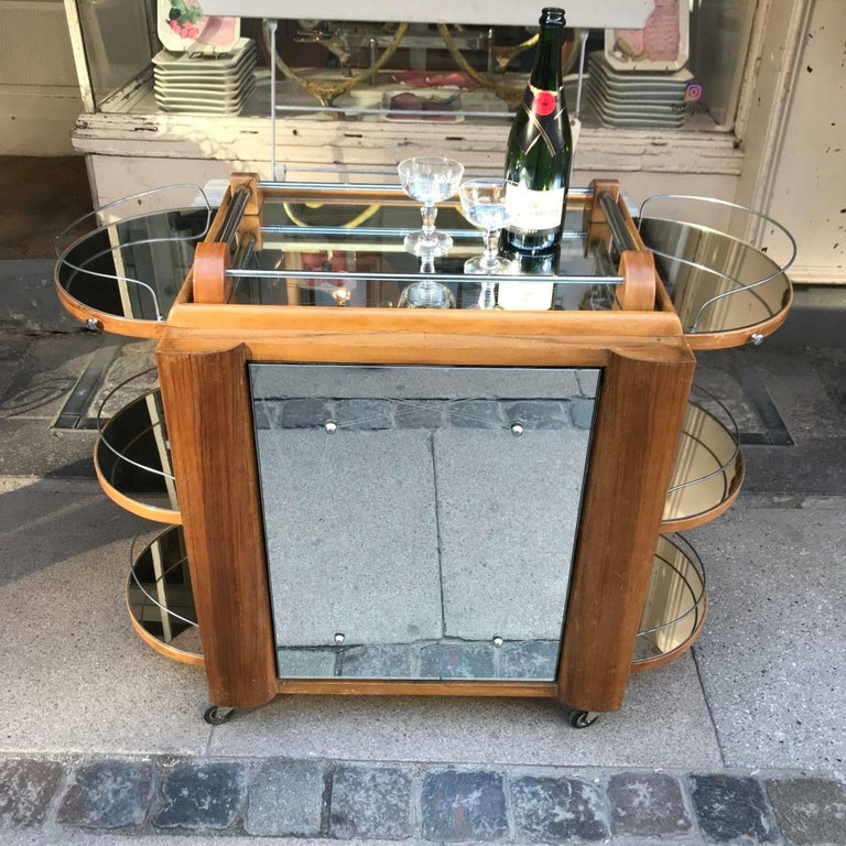 "This wonderful French bar / drinks cart displays all the hallmark elements of the Classic cross Atlantic ""ocean liner"" Art Deco design of the 1930s. The rounded ends, with the polished chrome railings, draw parrallels with a ships deck. The etched"