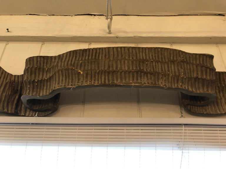A fabulously unusual found object sculpture, impressive in scale, having the shape of a rippled ribbon carved out of greyish brown natural finish wood. Looks like it came off the stern of a ship.