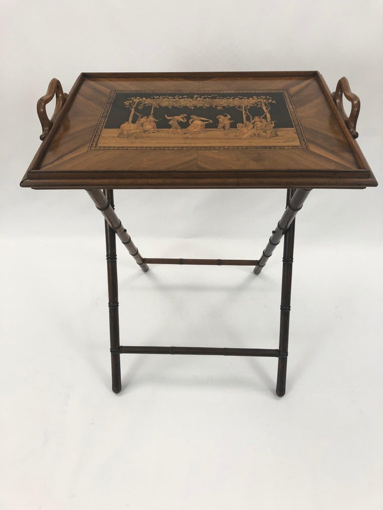 A splendid walnut inlaid tray table having a tray top on faux bamboo base with checkerboard on one side, and gorgeous intricate figural decoration on the other. The contrast of light and honey colored woods against a black background is especially