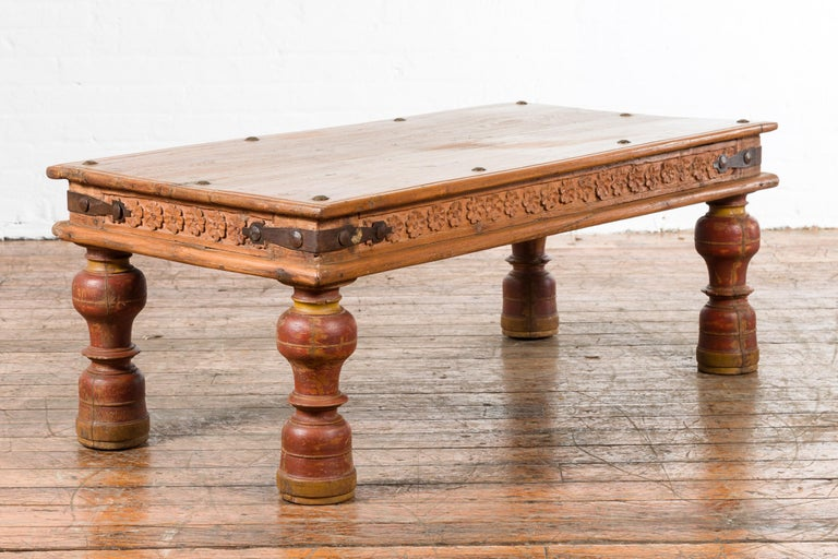 An Indian antique coffee table from the 19th century, with carved floral frieze, baluster legs and iron braces. Created in India during the 19th century, this wooden coffee table features a rectangular top with iron studs, sitting above an apron