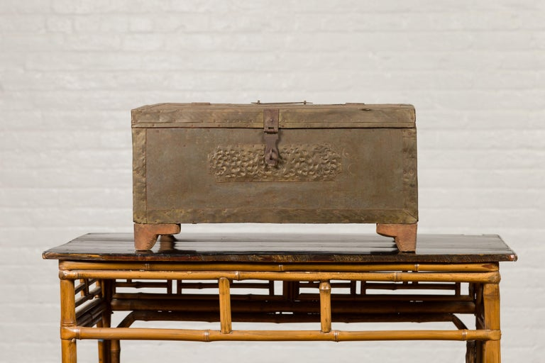 An antique Indian merchant's chest from the 19th century, with pierced geometric decor and weathered patina. Charming us with its clean lines and subtle decor, this merchant's chest features a rectangular lid lifting up in the front to reveal a