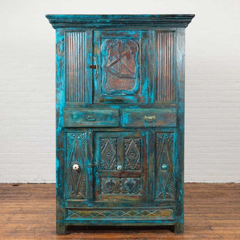An Indian antique painted cabinet from the 19th century, with royal teal patina, carved doors and drawers. Created in India during the 19th century, this unusual cabinet features a molded cornice sitting above a single cartouche-carved door, flanked