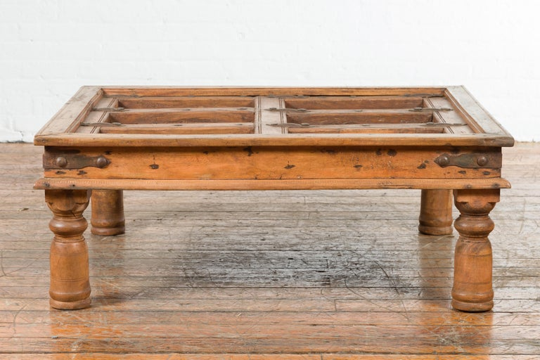 An Indian antique sheesham wood exterior courtyard door from the 19th century, made into a coffee table. Created in India during the 19th century, this sheesham wood courtyard door has been re-designed as a coffee table. The top, showcasing a