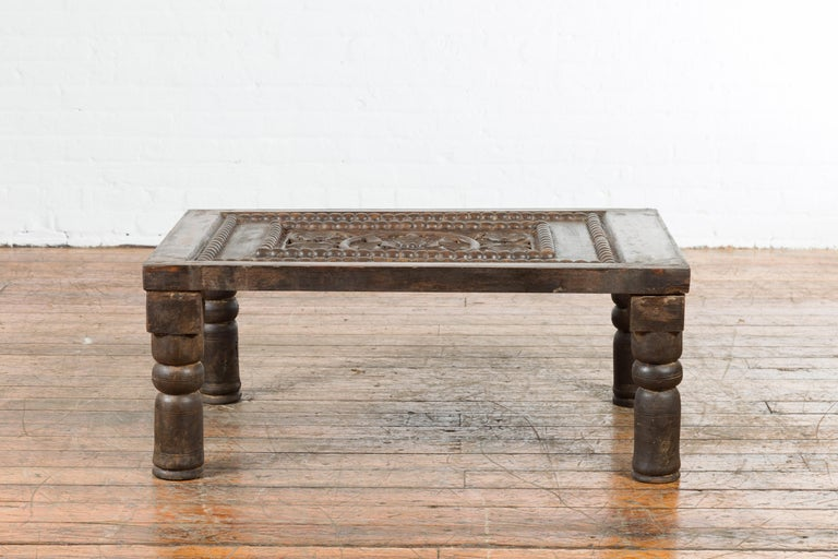 An Indian antique small coffee table from the 19th century, with carved wooden floral motifs and baluster legs. Created in India during the 19th century, this small coffee table features a rectangular top showcasing carved and pierced floral motifs