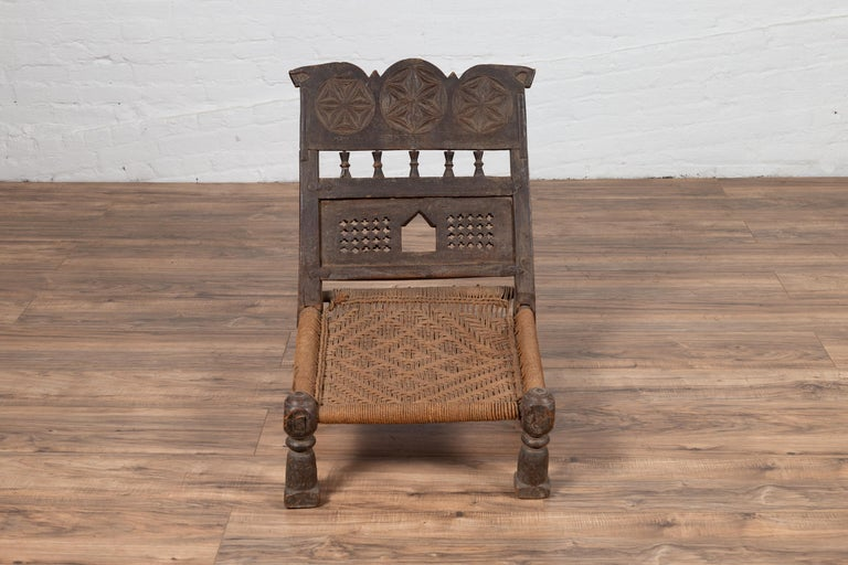 An old Indian rustic wooden low chair from the early 20th century, with handwoven rope seat and carved motifs. Charming our eyes with its rustic appearance, this low seat wooden chair features a short slanted back, adorned with three rosettes hand