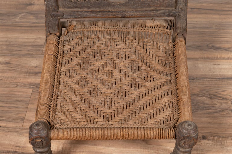 20th Century Indian Antique Rustic Low Seat Wooden Chair with Carved Rosettes and Rope Seat For Sale