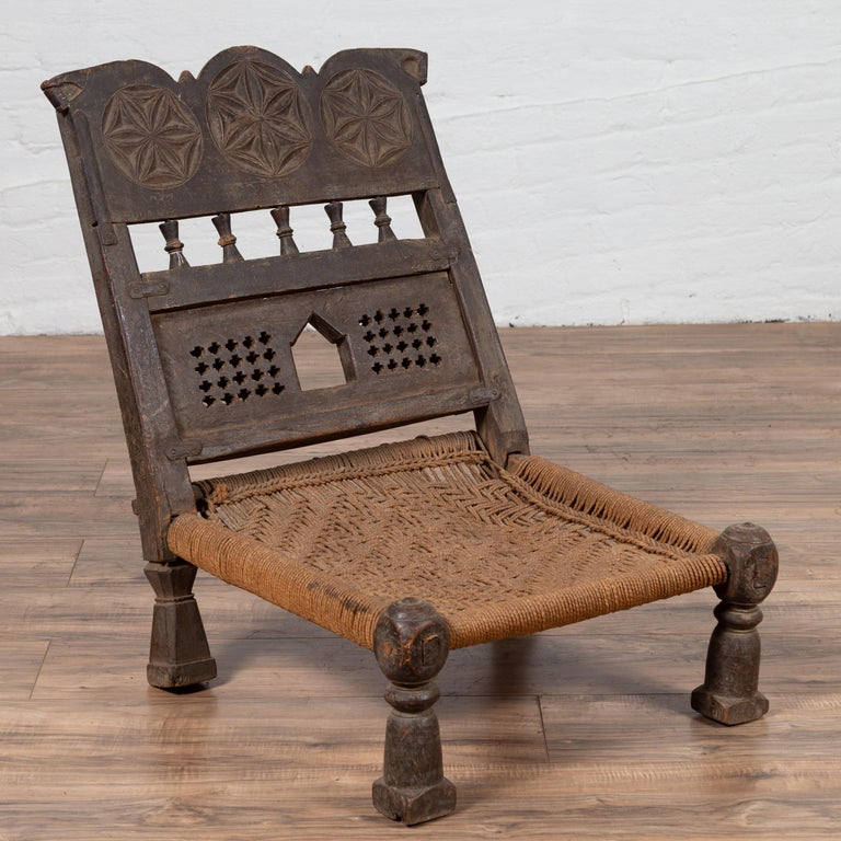 Indian Antique Rustic Low Seat Wooden Chair with Carved Rosettes and Rope Seat For Sale 4